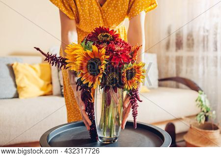 Woman Puts Vase With Yellow Orange Sunflowers And Red Zinnia Flowers On Table. Housewife Takes Care