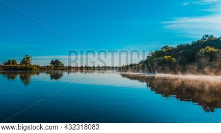 Aerial  view of a beautiful summer  landscape over river while dawn. Top view over river with a smooth water surface reflecting blue sky. Morning evaporation on a river while sunrise.