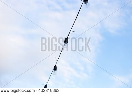 Lamps In Series With The Blue Sky Background . Street Electric Garland Against The Sky. One Row Of S