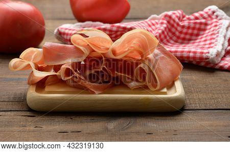 Sliced Thin Slices Of Prosciutto On Wooden Brown Board, Wooden Table Background