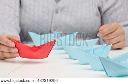 Group Of Blue Paper Boats Follows A Res Boat In Front Of A White Table. The Concept Of A Strong And