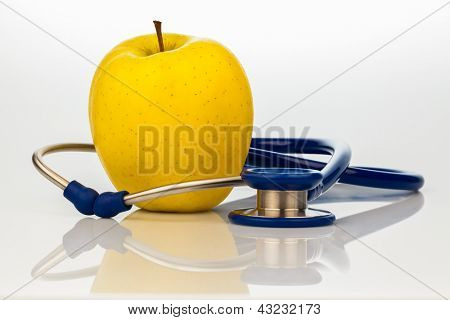 a stethoscope and an apple. symbolic of healthy eating.