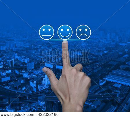 Hand Pressing Excellent Smiley Face Rating Icon Over Modern City Tower, Street, Expressway And Skysc