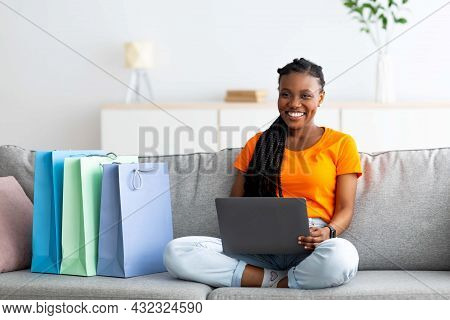 Home Shopping. Afro Woman With Credit Card And Laptop Buying Goods Online, Sitting On Couch With Sho