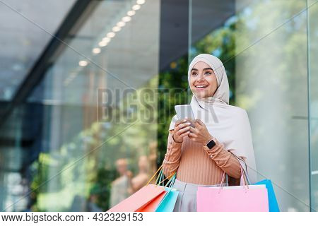 Surprised Smiling Cute Young Arabian Muslim Female In Hijab Enjoys Sale With Many Packets And Textin