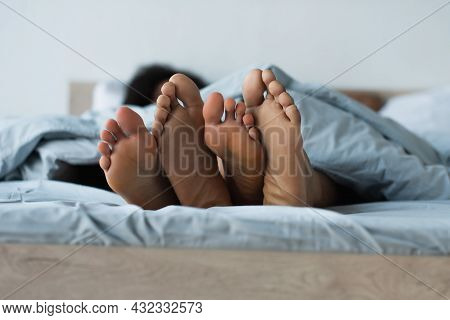 Feet Of Blurred African American Couple On Bed