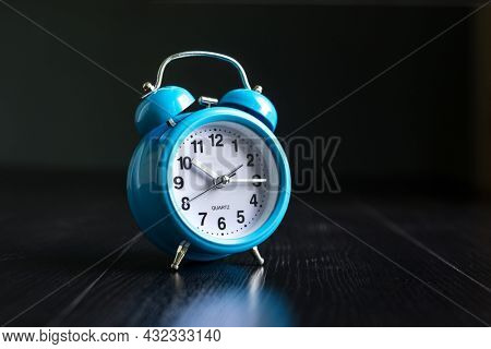 A retro, old style blue color alarm clock or buzzer. Classic analog clock with bell.