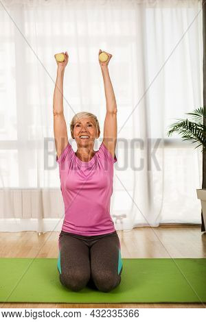 Portrait Of Senior Woman Sitting On Exercise Mat With Dumbbells At Home.