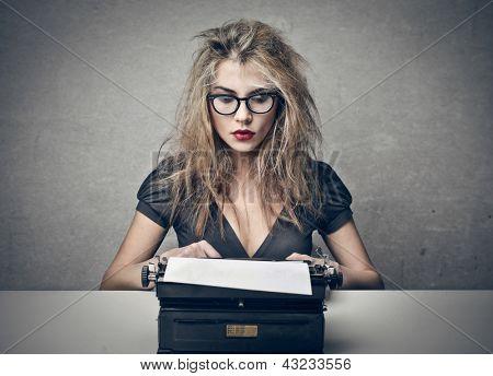 beautiful woman writes with a typewriter
