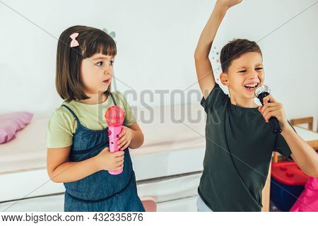 Portrait Of A Happy Children Singing Karaoke Through Microphone At Home.