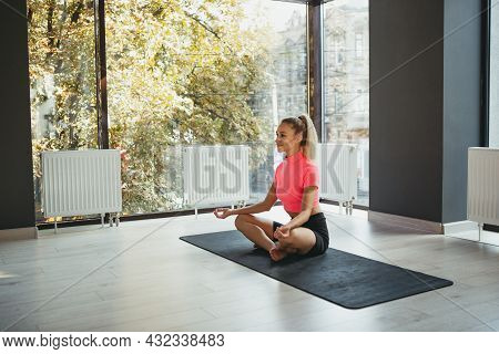 Portrait Of Young Slim Sportive Woman In Sportswear Doing Yoga Exercise On Sports Mat At Yoga Medita
