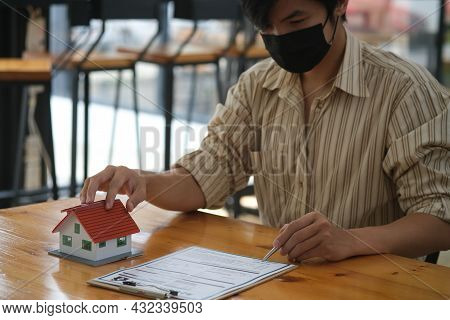 Portrait With A New House Ownership Signing A House Purchase Contract, Mortgage And Loan Ownership,