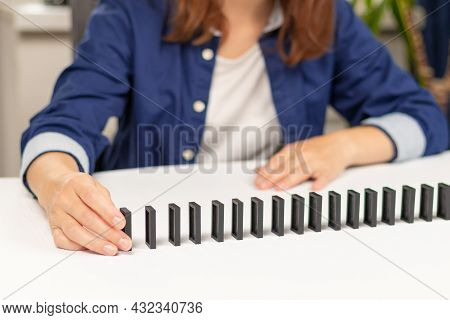 A Girl In A Blue Shirt Plays Dominoes At Home On A White Wooden Table. Selective Focus. Close-up