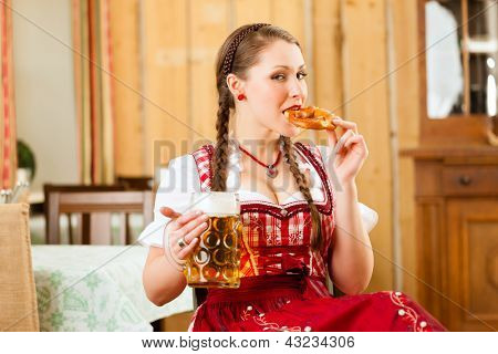 Young woman in traditional Bavarian Tracht in restaurant or pub with beer and steins and pretzel