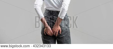 Woman Suffering From Hemorrhoids, Anal Pain. A Woman Holds His Hands To The Ass Feeling Pain. Hemorr