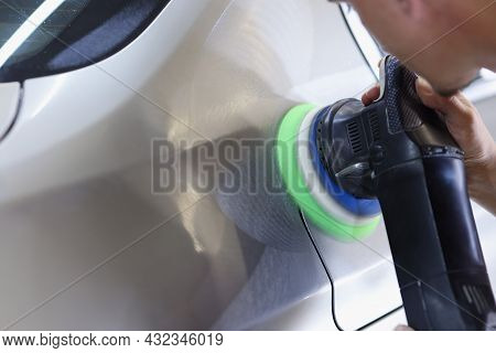 Man Holds Polisher In Hand And Polishes Car Closeup