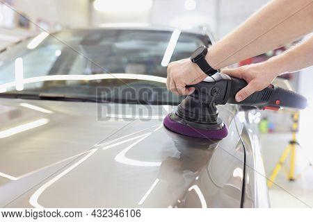 Man With An Orbital Polisher In Car Workshop Polishing Car Closeup