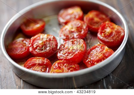 baking tray with cherry tomatoes drizzled with salt, olive oil and oregano