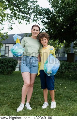 Cheerful Woman Hugging Son With Trash Bag Showing Like Outdoors