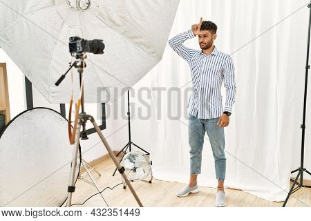 Arab young man posing as model at photography studio making fun of people with fingers on forehead doing loser gesture mocking and insulting.