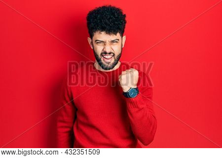 Young arab man with beard wearing casual red sweater angry and mad raising fist frustrated and furious while shouting with anger. rage and aggressive concept.
