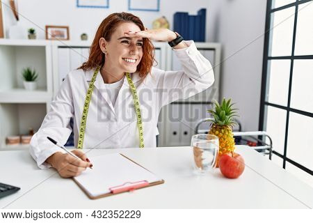 Young redhead woman nutritionist doctor at the clinic very happy and smiling looking far away with hand over head. searching concept.