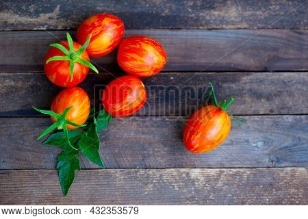 Many Small Red Tomatoes Lie On A Wooden Background