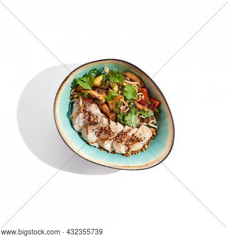 Healthy food in asian restaurant. Chicken breast grilled with roasted vegetables and coriander. Sliced Chicken fillet steak with teriyaki vegetables. Asian vegetables on wok with backed chicken