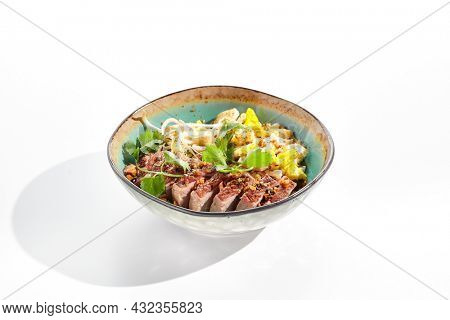 Pan asian traditional dish - fried rice with vegetables, shredded omelette and duck. Oriental wok with rice on white background. Nasi goreng with duck on isolated background with shadows