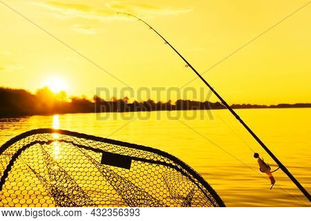 Summer Fishing On A Freshwater River. Fishing Tackle On An Orange Sunset Background