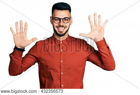 Young hispanic man with beard wearing business shirt and glasses showing and pointing up with fingers number ten while smiling confident and happy.