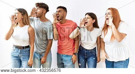 Group of young friends standing together over isolated background shouting and screaming loud to side with hand on mouth. communication concept.