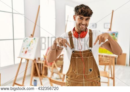 Young hispanic man at art studio looking confident with smile on face, pointing oneself with fingers proud and happy.