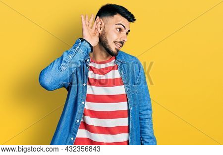 Young hispanic man with beard wearing casual denim jacket smiling with hand over ear listening an hearing to rumor or gossip. deafness concept.