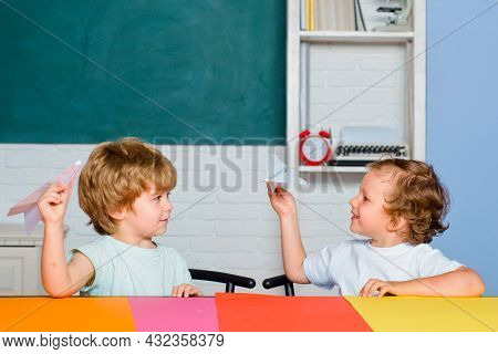 Funny Toddlers From Elementary School Hold Paper Plane Laughing And Smiling. Kids Funny Education. P