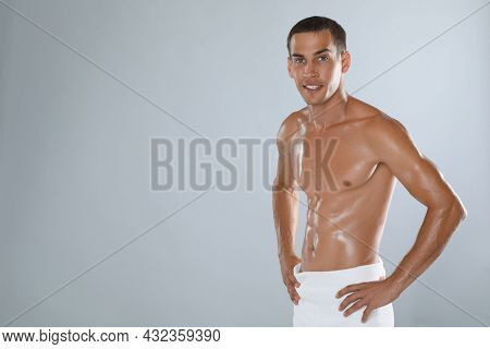 Handsome Shirtless Man With Slim Body And Towel Wrapped Around His Hips On Grey Background. Space Fo