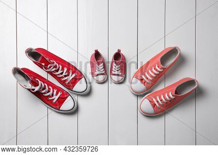 Stylish Sneakers For All Family Members On White Wooden Background, Flat Lay