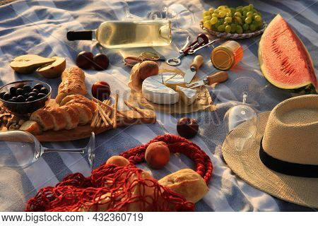 Many Different Tasty Snacks And Wine On Picnic Blanket