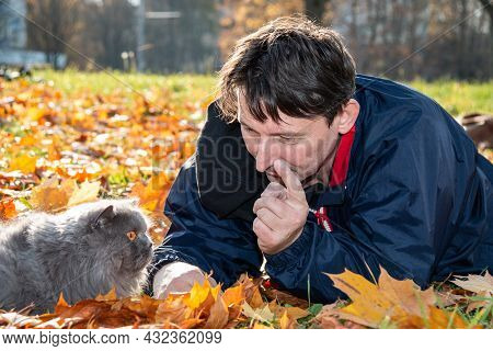 A Guy Is Talking With A Cat Threatening Him With A Finger While Lying On Yellow Autumn Leaves. Cat T