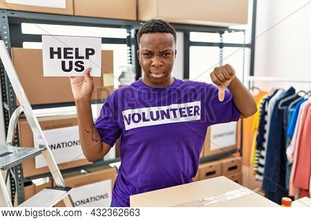 Young african volunteer man holding help us banner with angry face, negative sign showing dislike with thumbs down, rejection concept