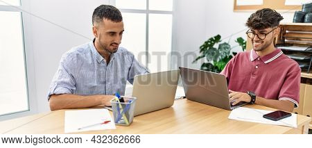 Two business workers smiling happy using laptop working at the office.