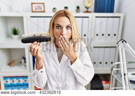 Beautiful blonde dentist woman comparing teeth whitening at the clinic covering mouth with hand, shocked and afraid for mistake. surprised expression