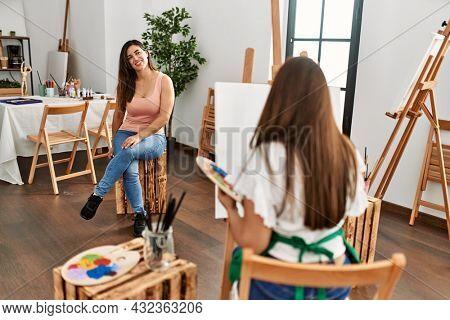 Back view portrait of artist painting at art studio.