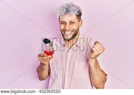 Young hispanic man with modern dyed hair holding luxury perfume screaming proud, celebrating victory and success very excited with raised arm