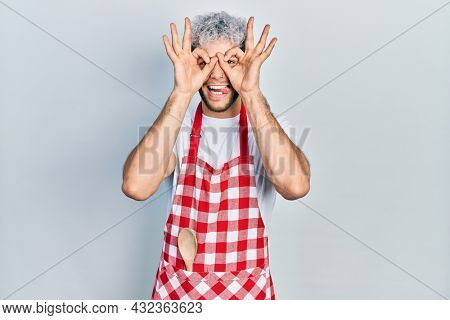 Young hispanic man with modern dyed hair wearing apron doing ok gesture like binoculars sticking tongue out, eyes looking through fingers. crazy expression.