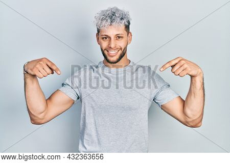Young hispanic man with modern dyed hair wearing casual grey t shirt looking confident with smile on face, pointing oneself with fingers proud and happy.