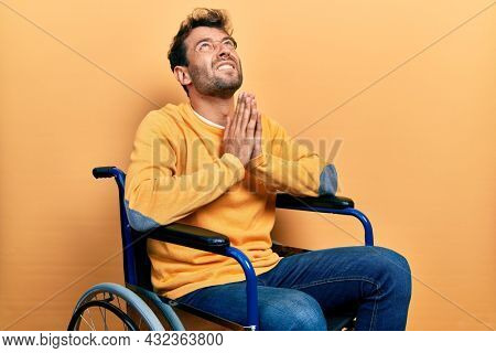 Handsome man with beard sitting on wheelchair begging and praying with hands together with hope expression on face very emotional and worried. begging.