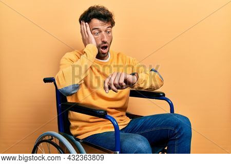 Handsome man with beard sitting on wheelchair looking at the watch time worried, afraid of getting late