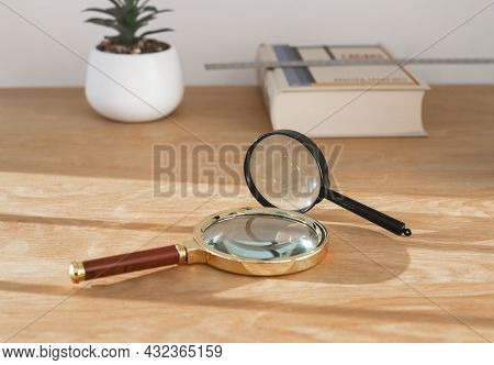Magnifying Lenses On Wood Desk With Book. Concept Of Exploration, Study And Research.