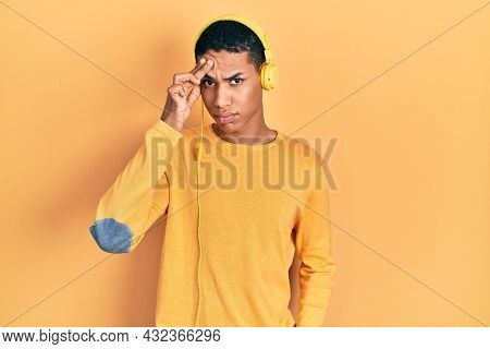 Young african american guy listening to music using headphones pointing unhappy to pimple on forehead, ugly infection of blackhead. acne and skin problem